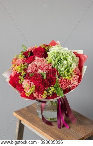Red And Green Flowers. Autumn Bouquet Of Mixed Flowers In Glass Vase On Wooden Table. The Work Of Th