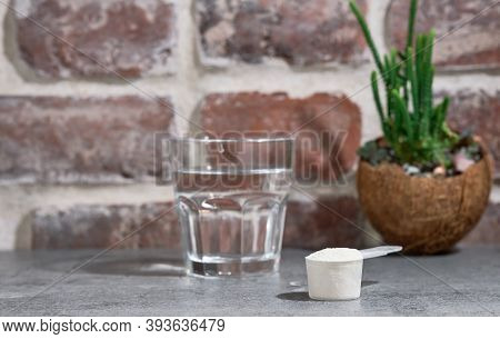 Collagen Protein Powder - Hydrolyzed, In Wooden Spoon On Stone Table, Next To Glass Of Water. Additi
