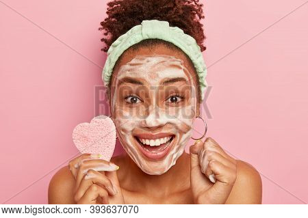Cropped Image Of Happy African American Woman Enjoys Relaxing Time, Washes Face With Soap Bubble, Fe