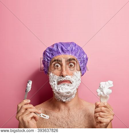 Puzzled European Man With Bugged Eyes, Holds Sharp Blade And Brush, Applies Shaving Foaming Gel On C