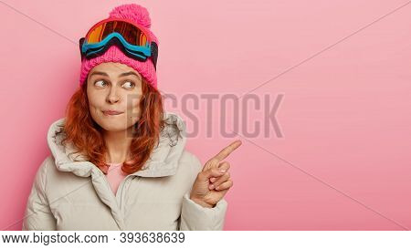 Redhead Dreamy Woman Points Away On Copy Space, Bites Lips, Spends Winter Holidays At Ski Resort, En