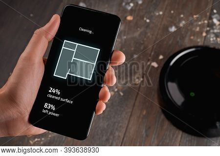 Man Using An App On His Phone To Control A Robotic Vacuum Cleane