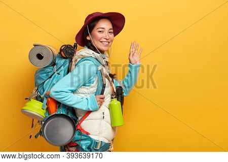 Hi To You. Positive Smiling Asian Woman Packpacker Has Cheerful Expression, Waves Palm At Camera, Ca