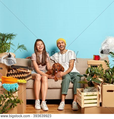 Happy Newlywed Couple Pose On Sofa With Favourite Pet, Have Good Mood After Moving In New Apartment,