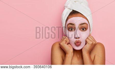 Cropped Shot Of Beautiful Dark Skinned Woman Keeps Lips Folded, Fists Near Cheeks, Has Bare Shoulder