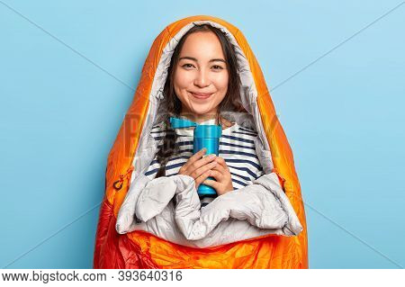 Photo Of Smiling Asian Woman With Plait, Wrapped In Sleeping Bag, Drinks Hot Tea From Thermos, Tries