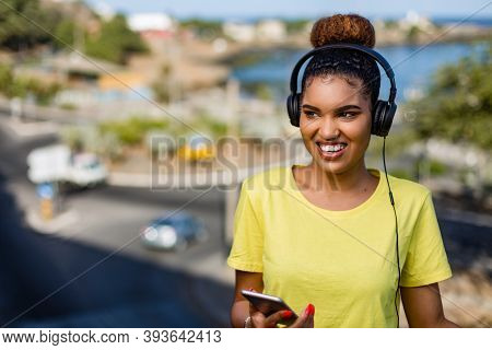 Pretty Young Black African American Woman Listening To Music With A Headphone Outdoor