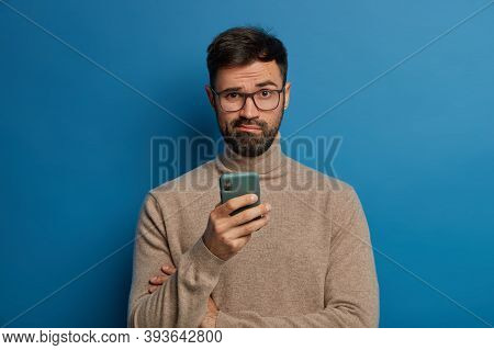 Puzzled Bearded Guy In Glasses Uses Modern Cell Phone, Smirks Face With Confusion And Misunderstandm