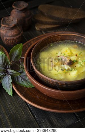 Wild Partridge Soup In A Pot With Vegetables On Old Wooden Background