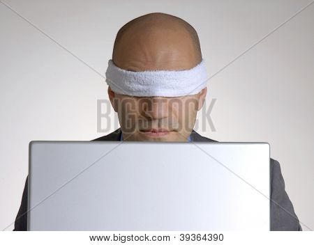 Bald head man blindfolded using a computer.