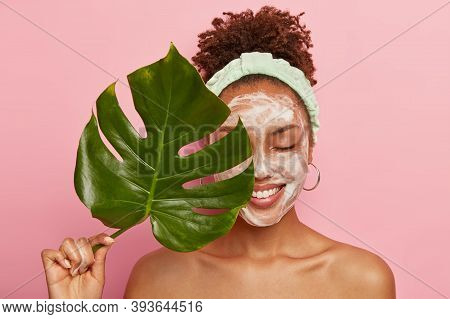 Portrait Of Happy African American Woman Covers Half Of Face With Green Leaf, Cleans Face, Washes Wi