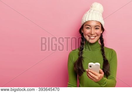 Image Of Lovely Brunette Girl Dials Telephone Number, Holds Modern Smartphone, Chats In Social Netwo