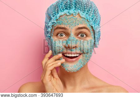 Close Up Portrait Of Surprised European Woman With Happy Look, Covers Face With Blue Granules Of Sea