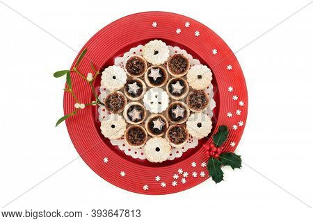 Luxury Christmas mince pies on a red plate with winter berry holly & mistletoe with decorative snowflakes on white background. Xmas food composition for the holiday season. Top view, copy space.