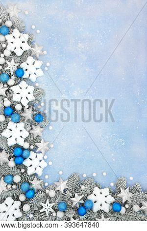 Magical Christmas & winter snowflake, star & blue bauble border with snow covered fir on pastel blue background. Xmas & New year festive composition. Flat lay, top view, copy space.