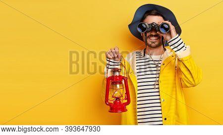 Horizontal Shot Of Happy Curious Male Traveler Looks Into Distance, Uses Binoculars, Holds Kerosene