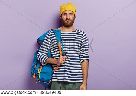 Displeased Unshaven Man Smirks Face, Has Unhappy Expression, Carries Tourist Rucksack, Being Tired O