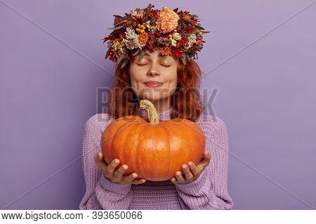 Horizontal Shot Of Pretty Redhead Woman Closes Eyes With Pleasure, Holds Ripe Orange Pumpkin, Demons