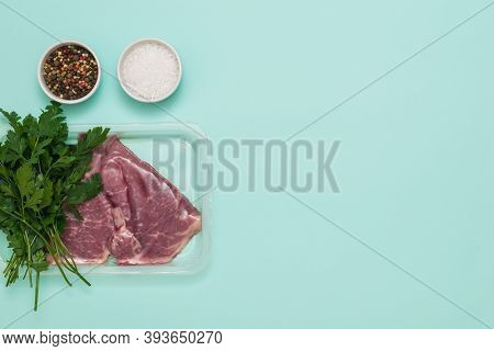 Salt, Pepper And Beef Meat In Vacuum Packaging On A Blue Background. Sealed Packaging For Meat.