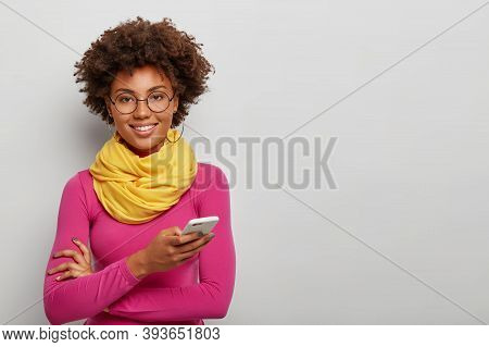 Isolated Shot Of Pleasant Looking Curly Woman Uses Mobile Phone For Chatting Online, Smiles Toothy,
