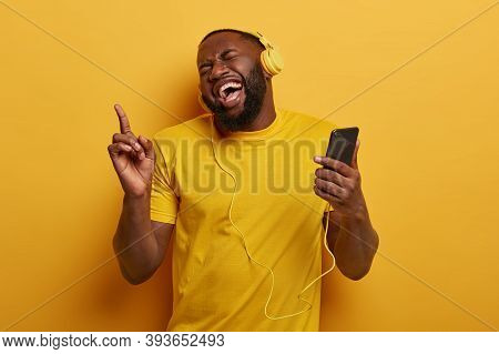Happy Dark Skinned Hipster Guy With Thick Beard, Laughs Joyfully, Points Index Finger Above, Holds M