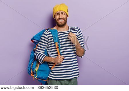 Photo Of Displeased European Man With Upset Expression, Clenches Teeth Nervously, Carries Blue Rucks