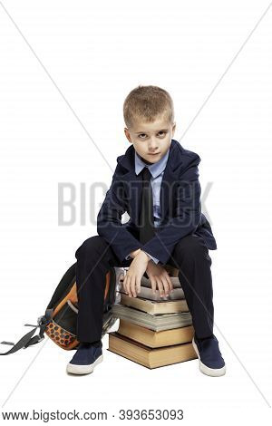 A Sad Schoolboy Sits On A Pile Of Books. Learning Difficulties. Isolated On White Background. Vertic
