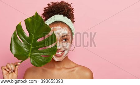 Pleased Dark Skinned Woman Stands Naked Alone, Looks Aside With Cheerful Expression, Holds Green Lea