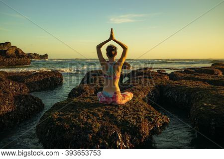 Young Woman Sitting On The Rock, Practicing Yoga At The Beach And Enjoying Ocean View. View From Bac
