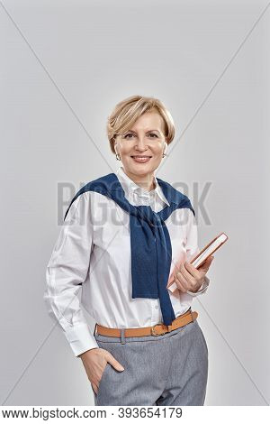 Portrait Of Elegant Middle Aged Caucasian Woman Wearing Business Attire Smiling At Camera, Holding H