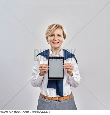 Portrait Of Middle Aged Caucasian Woman Wearing Business Attire Smiling At Camera, Holding Tablet Pc