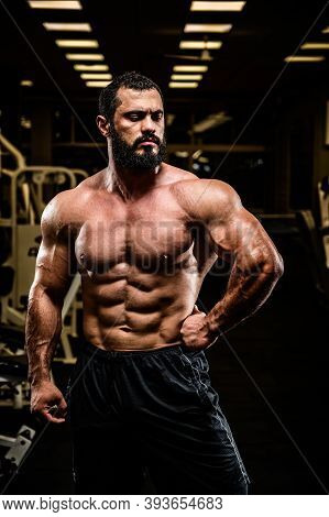 Handsome Bearded Young Athlete Man With Strong Muscular Physique Body In Dark Sport Gym