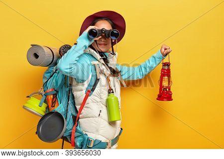 Horizontal Shot Of Curious Female Backpacker Explores Tourist Destination, Uses Binoculars, Dressed