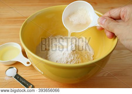Hand Pouring Yeast With Water Into The Bowl Of Wholemeal Flour
