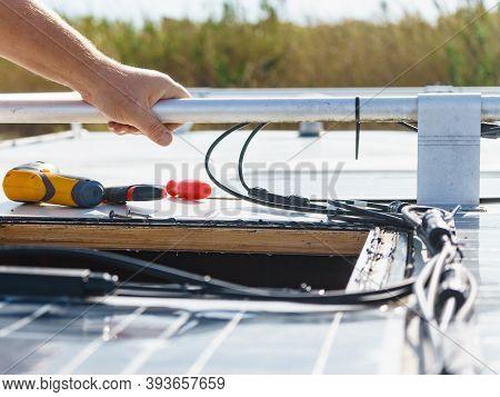 Male Hands Installing Flexible Solar Panel On Rv Campervan Or Repair Camper Car Roof.