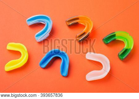 Many Boxing Mouthguards Of Different Colors, Lies On An Orange Background