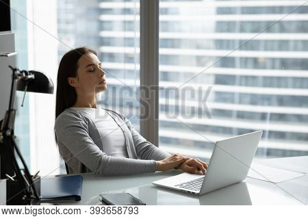 Peaceful Woman Employee With Closed Eyes Leaning Back On Chair