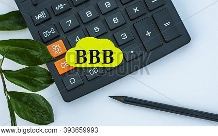 Bbb (better Business Bureau) - Word On A Yellow Note Sheet On A White Background With A Calculator,