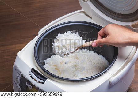 Woman Hand Is Scooping Jasmine Rice Cooking In Electric Rice Cooker With Steam. Thai Jasmine Rice.