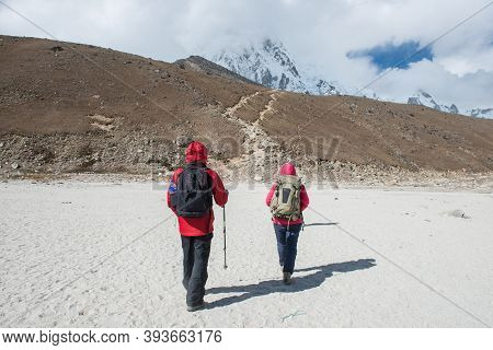 Back View Of Two Trekkers Walking On The Way To Kala Patthar (5,643 M) One Of Highlights Of An Evere