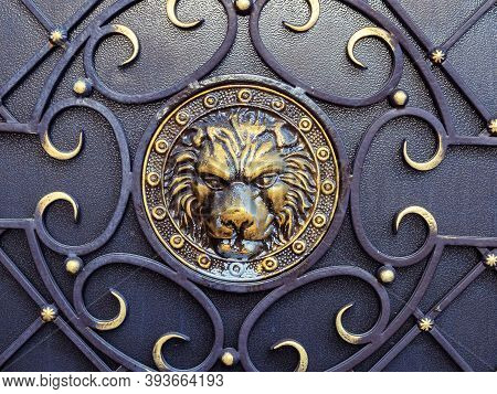 Gilded Lion Head With Forged Ornament On A Black Iron Surface
