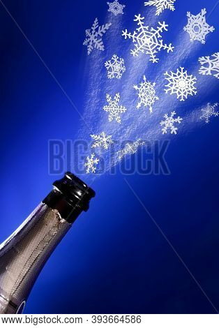 Snowflakes flying out of a bottle of champagne. Isolated conceptual photo-illustration on blue background