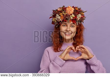 Lovely Pretty Ginger Girl Demonstrates Love Sign, Shapes Heart With Hands, Has Friendly Expression,