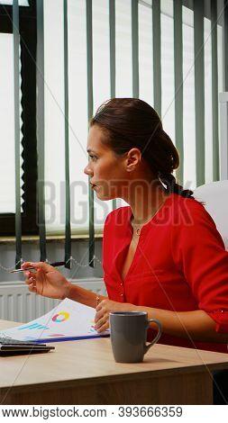 Young Employee Checking Clipboard Information Looking On Pc Desktop. Hispanic Entrepreneur Working I