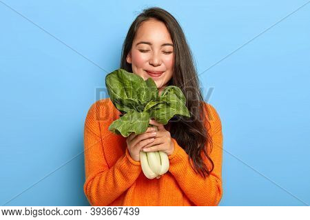 Horizontal View Of Pleased Korean Woman Holds Freshly Leafy Vegetable, Enjoys Eating Nutrient Food C