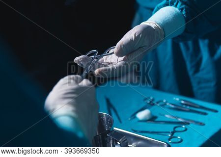 Two Surgeons Working In Operating Room, One Hand Over Surgical Equipment To Another. Surgeons Hands