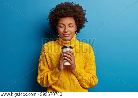Satisfied Young Afro Woman Adores Drink, Holds Takeaway Coffee, Closes Eyes, Wears Yellow Sweater, I