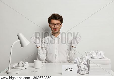 Zen Like. Relaxed Bearded Stylish Man In White Formal Outfit Meditates At Cozy Workplace, Keeps Calm