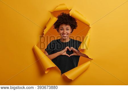 Pleased Dark Skinned Young Woman Shows Heart Symbol, Shapes Love Sign With Hands, Smiles Happily, We