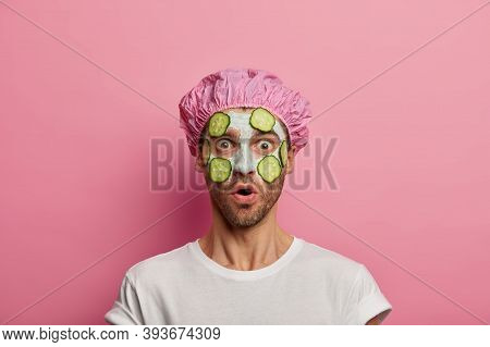Scared Fearful Man With Surprised Expression, Applies Clay Mask With Slices Of Green Cucumber, Keeps